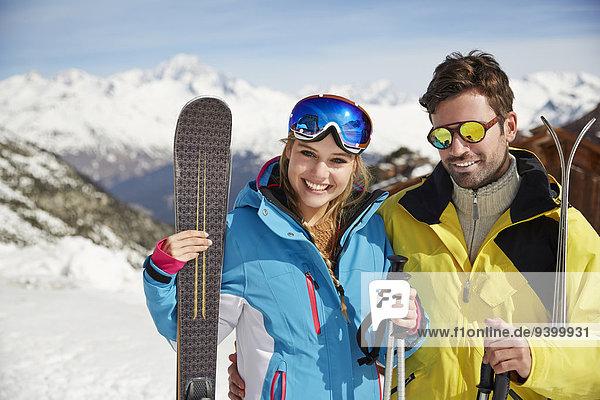 Paar tragende Skier auf dem Berggipfel