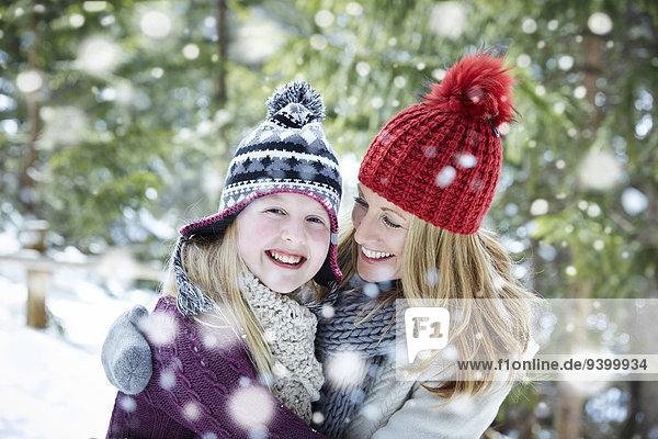 Mutter und Tochter beim Umarmen im Schnee