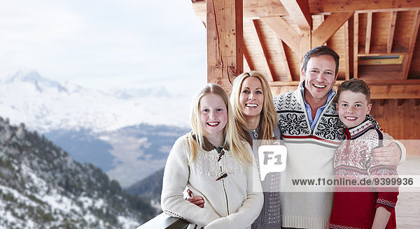Familie lächelt gemeinsam auf dem Balkon