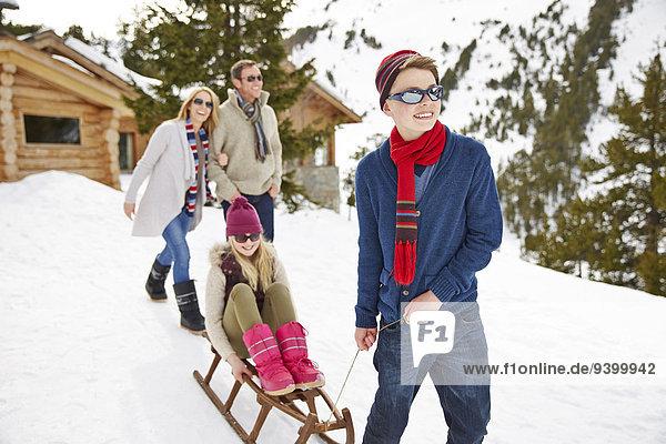 Bruder zieht Schwester auf Schlitten im Schnee