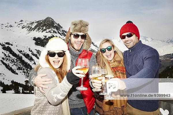 Paare feiern mit Getränken im Schnee