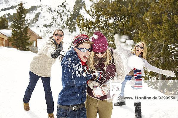 Familie beim gemeinsamen Schneeballschlachten