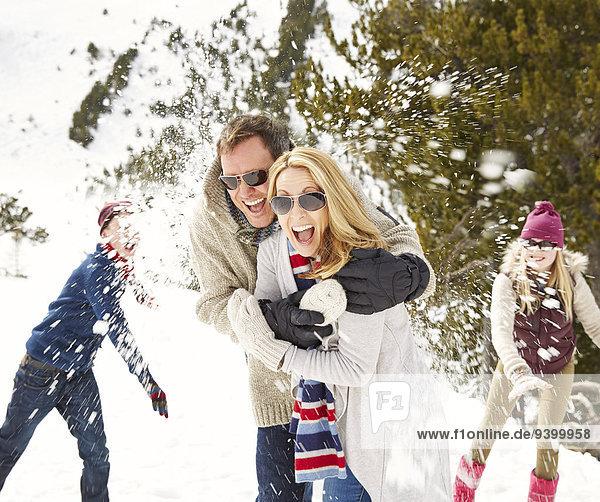 Familie bei einer Schneeballschlacht im Schnee
