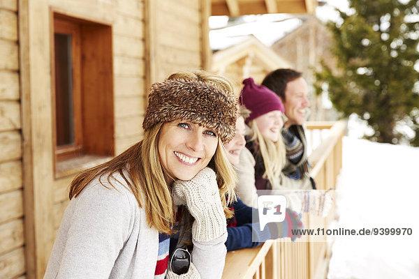 Mutter steht auf dem verschneiten Balkon mit Familie