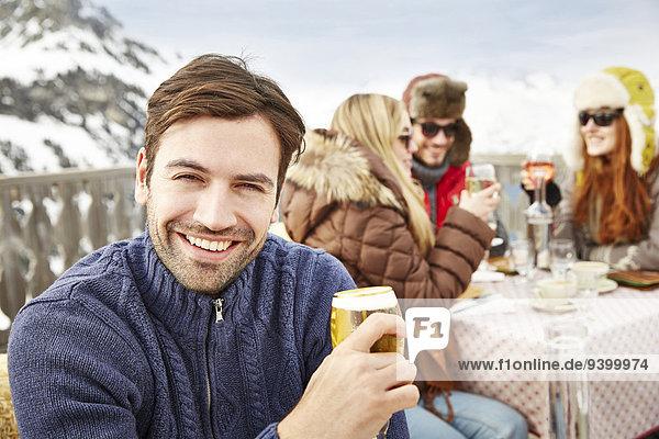 Mann genießt Getränke mit Freunden