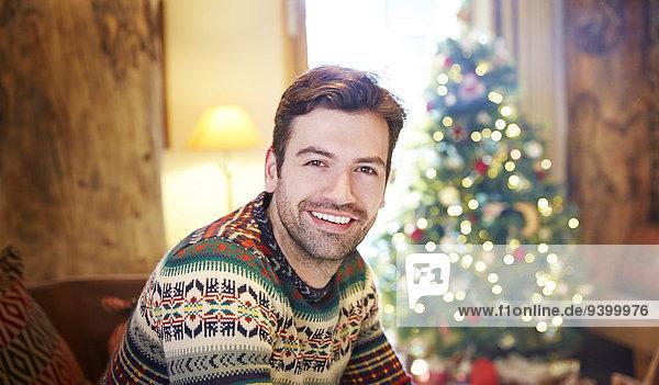Mann auf der Couch am Weihnachtsbaum sitzend