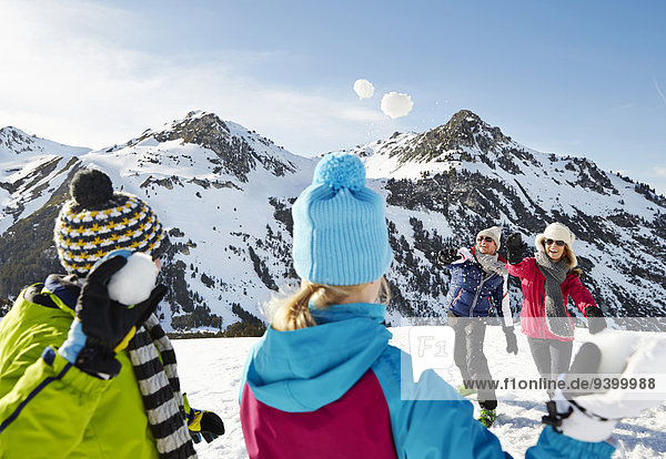 Familie bei einer Schneeballschlacht am Berg