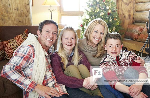Familie sitzt im Wohnbereich zusammen