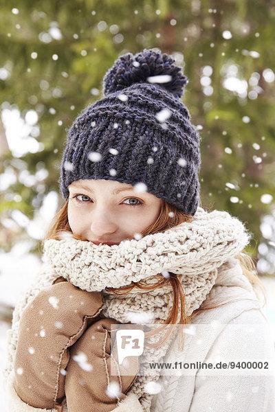 Frau mit Schal und Hut im Schnee