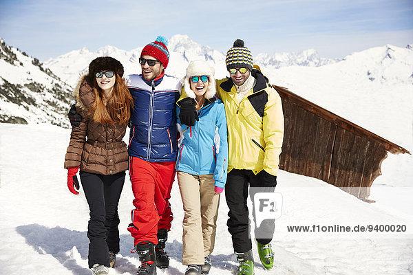 Freunde  die zusammen im Schnee spazieren gehen.