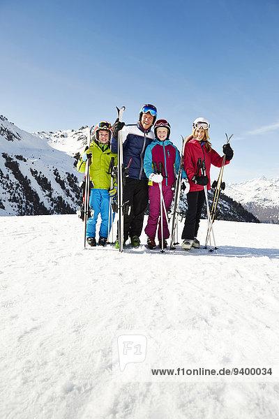 Familie hält Skier auf Berggipfel zusammen