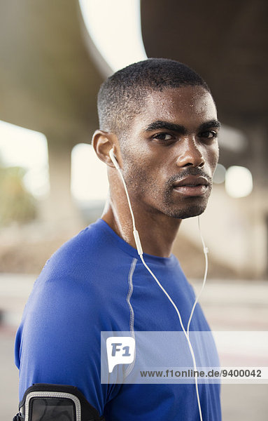Mann mit Kopfhörer beim Training auf der Straße in der Stadt