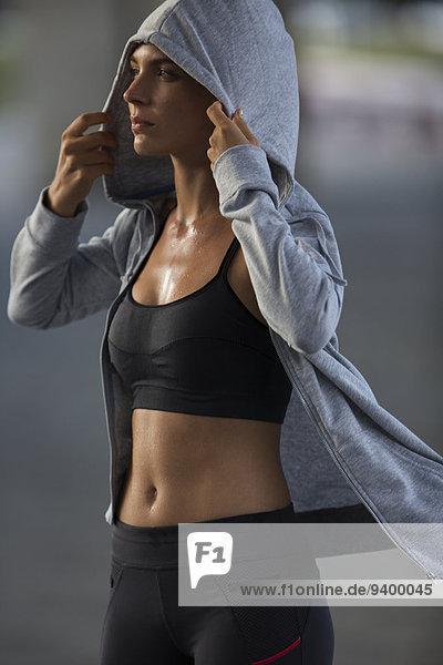 Frau zieht sich nach dem Training ein Sweatshirt an