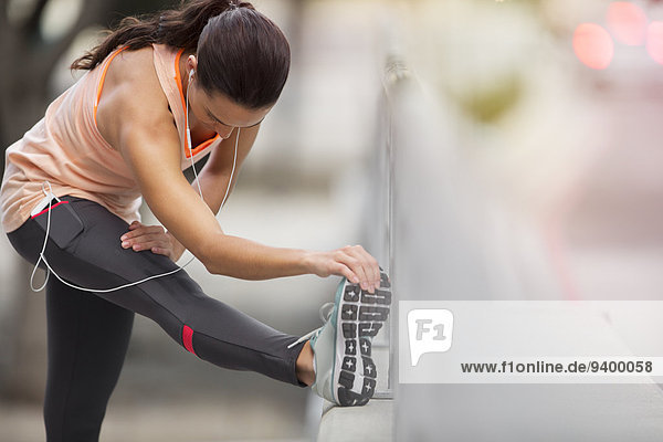 Frau streckt ihr Bein vor dem Training aus