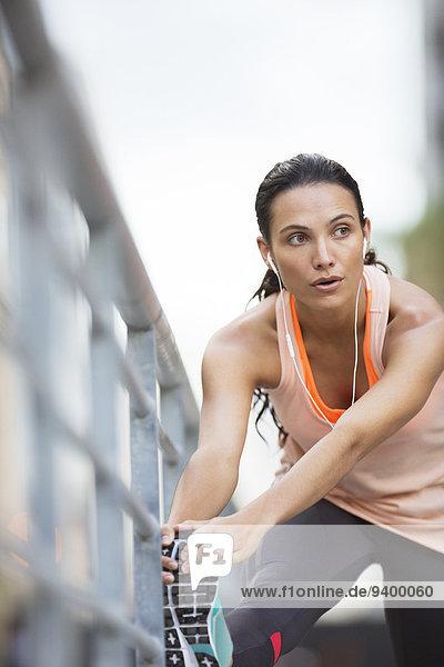 Frau streckt ihre Beine vor dem Training aus