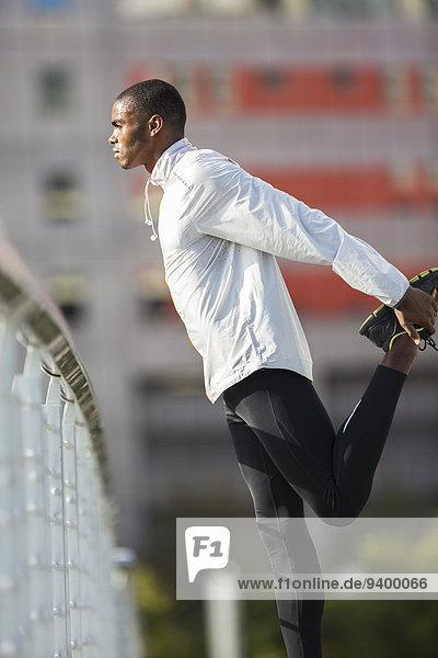 Mann  der vor dem Training die Beine streckt