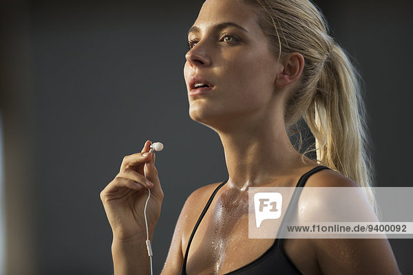 Frau nimmt nach dem Training Kopfhörer heraus