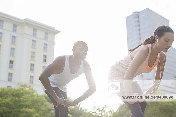 Paar Stretching vor dem Training auf der Stadtstraße