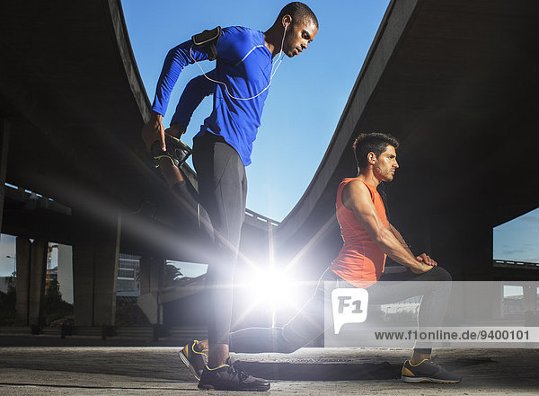 Männer, die sich vor dem Training auf der Straße ausstrecken.
