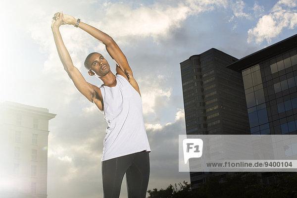 Mann streckt sich vor dem Training auf der Stadtstraße