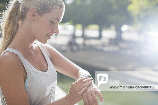 Frau schaut auf die Uhr  bevor sie in der Stadt trainiert.