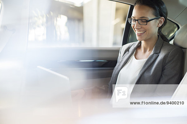 Businesswoman using laptop in car back seat