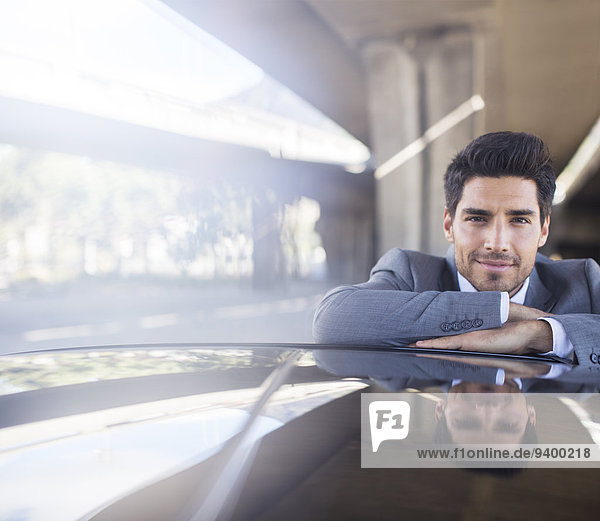Geschäftsmann ruht auf dem Auto in der Tiefgarage