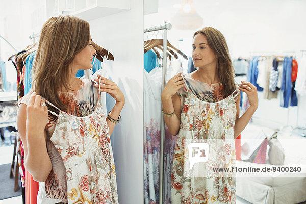 Frau bewunderndes Kleid im Ladenspiegel