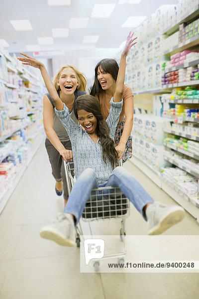 Frauen spielen mit Einkaufswagen im Lebensmittelgeschäft