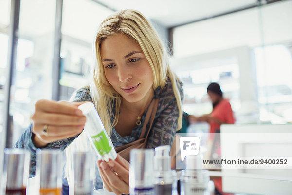 Frau untersucht Hautpflegemittel in der Apotheke