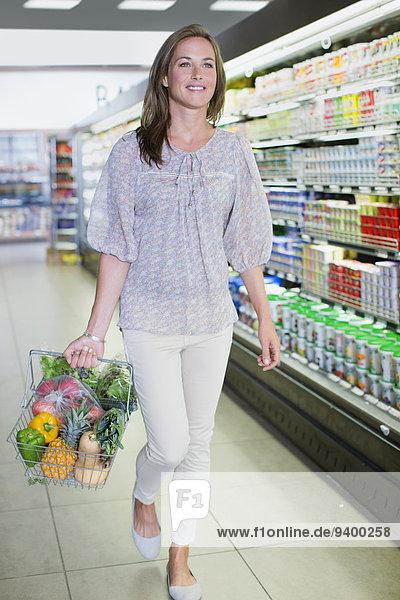 Frau mit vollem Einkaufskorb im Lebensmittelgeschäft
