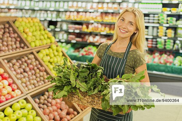Sekretärin mit Warenkorb im Lebensmittelgeschäft
