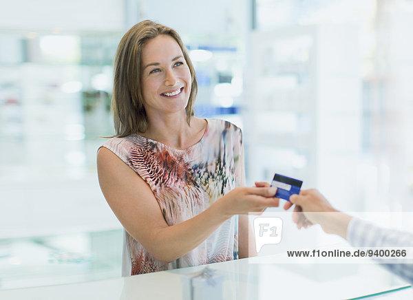 Frau bezahlt mit Kreditkarte in der Apotheke