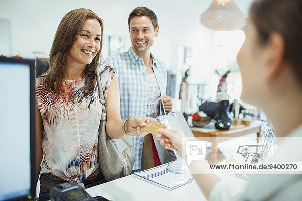 Paare zahlen mit Kreditkarte im Bekleidungsgeschäft