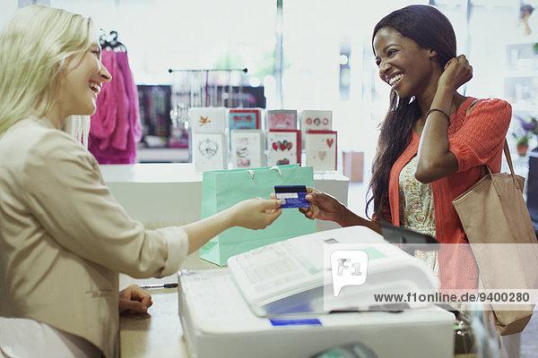 Frau bezahlt mit Kreditkarte im Geschäft