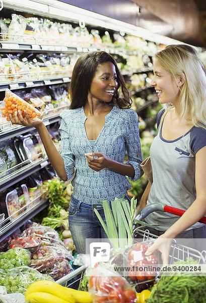 Frauen beim gemeinsamen Einkaufen im Lebensmittelgeschäft Frauen beim gemeinsamen Einkaufen im Lebensmittelgeschäft