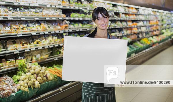 Angestellter  der eine leere Karte in der Produktionsabteilung des Lebensmittelgeschäfts hält.