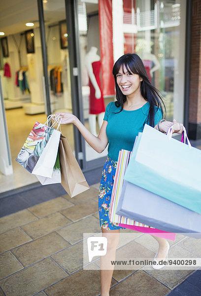 Frau mit Einkaufstaschen in der Stadtstraße
