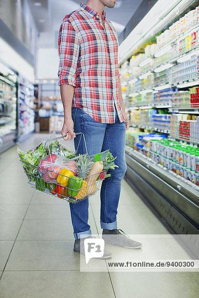 Mann mit vollem Einkaufskorb im Lebensmittelgeschäft