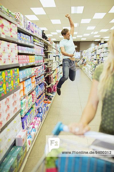 Mann springt vor Freude im Lebensmittelgeschäft