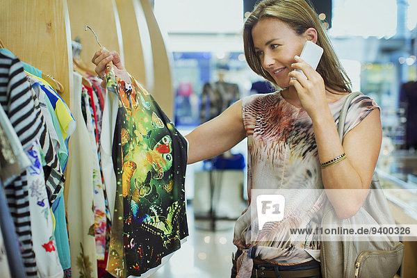 Frau spricht am Handy und Einkaufen im Bekleidungsgeschäft