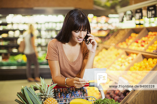 Woman talking on cell phone and shopping in grocery store