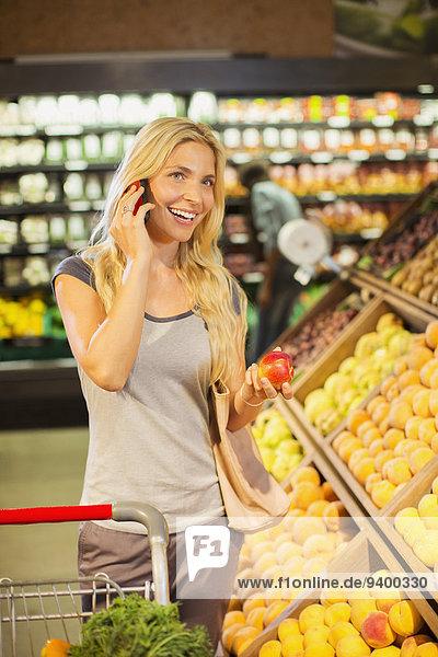 Frau beim Telefonieren und Einkaufen im Lebensmittelgeschäft