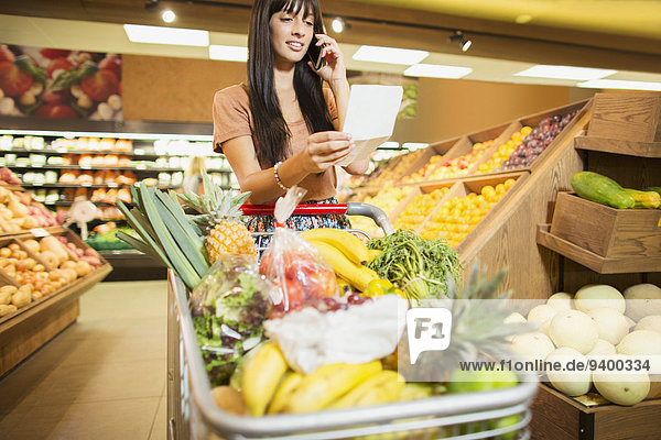 Frau spricht am Handy im Lebensmittelgeschäft