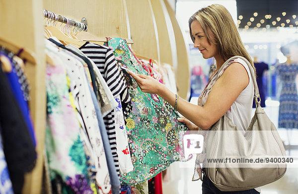 Frau überprüft Preisschilder beim Einkaufen im Bekleidungsgeschäft