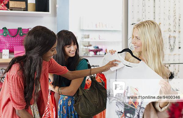 Frauen beim gemeinsamen Einkaufen im Bekleidungsgeschäft Frauen beim gemeinsamen Einkaufen im Bekleidungsgeschäft
