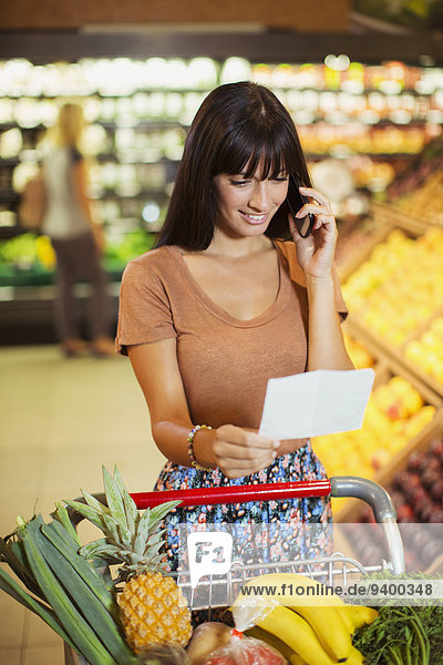 Woman talking on cell phone while shopping in grocery store