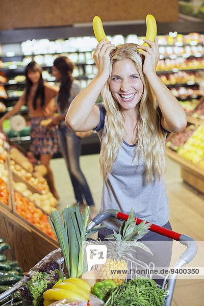 Frau spielt mit Bananen beim Einkaufen im Lebensmittelgeschäft