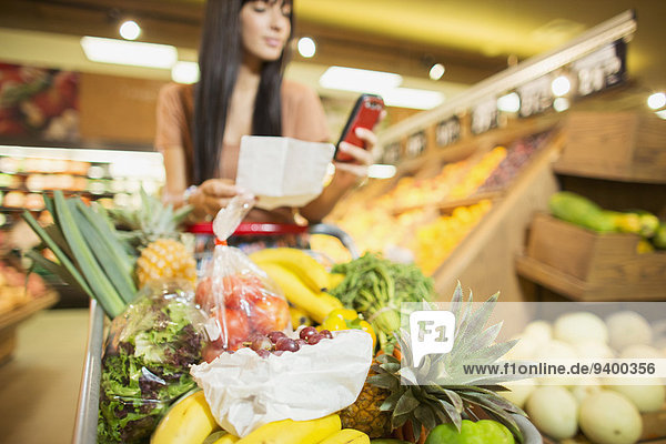 Frau überprüft Einkaufsliste im Lebensmittelgeschäft