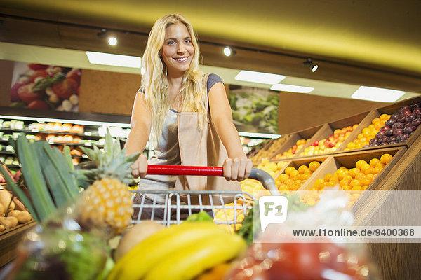 Frau schiebt vollen Einkaufswagen im Lebensmittelladen